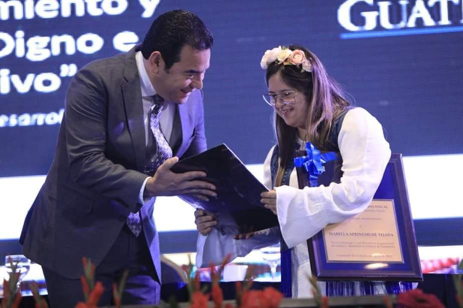 Diseñadora Isabella Springmuhl Tejada recibe galardon de manos del presidente Jimmy Morales. Foto Gobierno de Guatemala